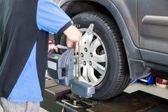 Werktuigkundige die het apparaat van de wielgroepering op het wiel vastmaken op workshop Stock Foto's