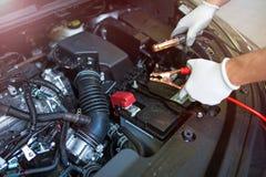 Werktuigkundige die verbindingsdraadkabels gebruiken om een auto te beginnen Royalty-vrije Stock Foto