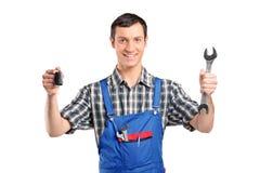 Werktuigkundige in eenvormige holding een een autosleutel en moersleutel Royalty-vrije Stock Foto's