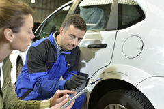 Werktuigkundige en verzekeraar die controle van autoschade doen stock afbeelding