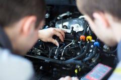 Werktuigkundigen bij reparatiewerkplaats twee zekere werktuigkundigen die aan een motor van een auto werken Stock Fotografie