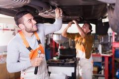 Werktuigkundigen die auto van cliënt herstellen Stock Afbeeldingen