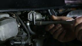 Werktuigkundigenhand unscrewes de slang van brandstoftank op motorfiets stock video