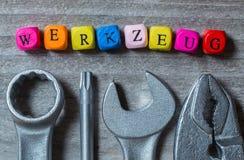 Werkzeug w niemiec narzędzia listu narzędziu na szarym drewnianym visu i sześcianie Zdjęcie Stock