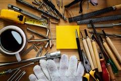 Werkzeugausrüstung mit Kaffee und Notizblock auf Holz Stockbild