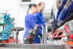 Werkzeuge in der Garage oder in der Werkstatt mit Mechanikern lizenzfreie stockfotos
