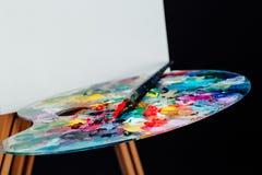 Werkzeuge des Künstlers Brushes, hölzerner Gestellstativ, Palette bunt Schwarzer Hintergrund, Studio, niemand stockbild