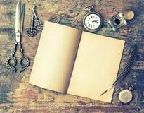 Werkzeuge des offenen Buches und des Antikenschreibens auf Holztisch Getrennt auf einem weißen Hintergrund Stockfoto