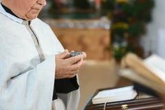 Werkzeuge für Babytaufe eley in den Händen eines Priesters Catholicism, das Konzept des Christentums lizenzfreie stockfotografie
