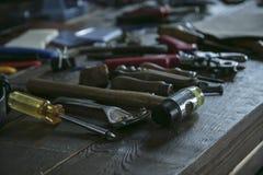 Werkzeuge für das Leder, das an Holztisch arbeitet Toolkit für lederne Arbeitskraft Lizenzfreie Stockbilder