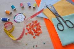 Werkzeuge für das Nähen für Hobby stellten auf Draufsicht des Holztischhintergrundes ein Nähender Satz Thread, Nadeln und Stoff Lizenzfreie Stockbilder