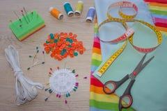 Werkzeuge für das Nähen für Hobby stellten auf Draufsicht des Holztischhintergrundes ein Nähender Satz Thread, Nadeln und Stoff Stockfotografie