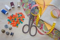 Werkzeuge für das Nähen für Hobby stellten auf Draufsicht des Holztischhintergrundes ein Nähender Satz Thread, Nadeln und Stoff Lizenzfreies Stockbild