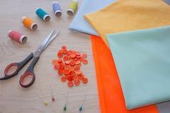 Werkzeuge für das Nähen für Hobby stellten auf Draufsicht des Holztischhintergrundes ein Nähender Satz Thread, Nadeln und Stoff Stockfotos