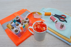 Werkzeuge für das Nähen für Hobby stellten auf Draufsicht des Holztischhintergrundes ein Thread, Nadeln, Scheren und Stoff Lizenzfreie Stockfotos
