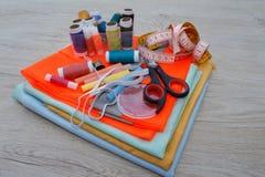 Werkzeuge für das Nähen für Hobby stellten auf Draufsicht des Holztischhintergrundes ein Thread, Nadeln, Scheren und Stoff Stockfoto