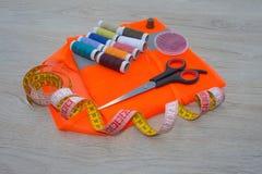 Werkzeuge für das Nähen für Hobby stellten auf Draufsicht des Holztischhintergrundes ein Thread, Nadeln und Stoff Lizenzfreies Stockfoto