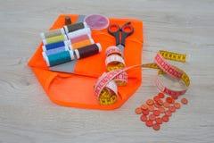 Werkzeuge für das Nähen für Hobby stellten auf Draufsicht des Holztischhintergrundes ein Thread, Nadeln und Stoff Lizenzfreie Stockfotos