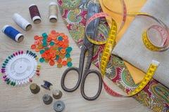 Werkzeuge für das Nähen für Hobby stellten auf Draufsicht des Holztischhintergrundes ein Thread, Nadeln und Stoff Stockbilder