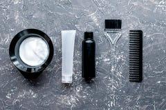 Werkzeuge für Haarfärbemittel im Friseursalon auf Draufsicht des grauen Hintergrundes Stockfotografie