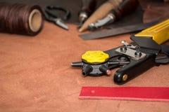 Werkzeuge f?r das Lederin handarbeit machen und die St?cke braunes Leder stockbilder