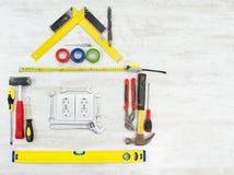 Werkzeuge in Form des Hauses, Haus über hölzernem weißem Hintergrund Lizenzfreie Stockfotos