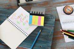 Werkzeuge, Rahmen, Notizblock, Gl?ckwunsch auf einem Holztisch lizenzfreies stockbild