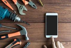 Werkzeuge und intelligentes Telefon auf hölzernem Hintergrund stockfotografie