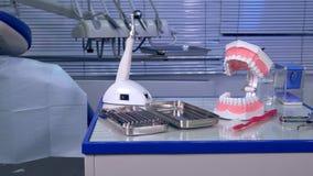 Werkzeuge und Modell des Kiefers in der Arbeitsplatzzahnarztklinik stock footage