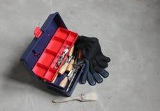 Werkzeugkasten mit Handschuhen und Bürste Stockfoto