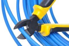 Werkzeugzangen, die blaues Kabel schneiden Stockfotos