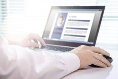 Werkzoekende en kandidaat die zijn samenvatting en cv met laptop schrijven stock afbeelding