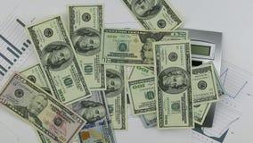 Werp dollars op de grafiek met calculator en pen Het werpen van Geld onderaan lijst stock footage