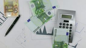 Werp euro op de grafiek met calculator en pen Het werpen van Geld onderaan lijst stock video