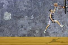 Werpt de basketbal in hand mens die een basketbalhoepel op de houten zolder vloer van de Achtergrondpleistermuur met het patroon  stock foto