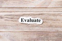 Werten Sie vom Wort auf Papier aus Konzept Wörter von Evaluate auf einen hölzernen Hintergrund stockbild