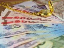 Wertvolle Zeit mit Geld, Banknoten und Golduhr mit Halskette Lizenzfreie Stockfotos
