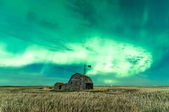 Werveling van Noordelijke Lichten over uitstekende schuur in Saskatchewan, Canada royalty-vrije stock afbeelding