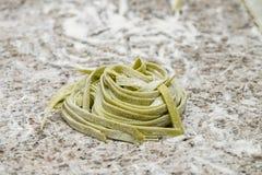 Wervelingen van gekookte spaghetti op de lijst met bloem royalty-vrije stock foto