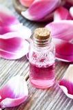 Wesentlich-Flasche mit den weichen rosa Blumenblättern stockfoto