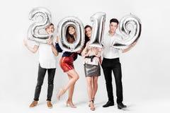 Wesoło przyjaciele dwa dziewczyny i dwa faceta ubierających w eleganckich ubraniach trzymają balony w formie liczb 2019 na a obrazy royalty free