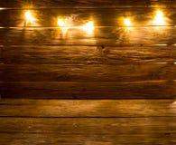 Wesoło boże narodzenia! Bożonarodzeniowe światła tło na brown nieociosanym drewnianym tle fotografia stock