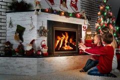 Wesoło boże narodzenia i Szczęśliwi wakacje! Mama i dwa małego syna siedzimy i relaksujemy pod choinką grabą, grżemy ich ręki zdjęcie stock