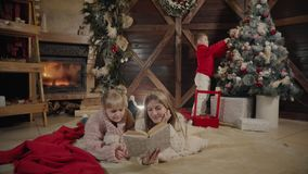 Wesoło boże narodzenia i Szczęśliwy nowy rok Piękna rodzina w Xmas wnętrzu Ładnych potomstw macierzysty czytanie książka ona zdjęcie wideo