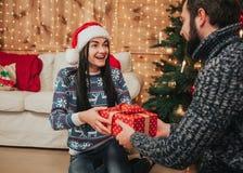Wesoło boże narodzenia i Szczęśliwy nowy rok Potomstwo pary odświętności wakacje w domu Szczęśliwy młodego człowieka i kobiety da Fotografia Royalty Free
