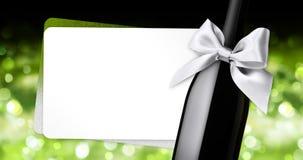Wesoło boże narodzenia wita prezent kartę z wino butelki srebra tasiemkowym łękiem na zieleni zamazującej zaświecają tło royalty ilustracja