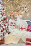 Wesoło bożych narodzeń i Szczęśliwych wakacji małego dziecka Śliczne dziewczyny dekoruje białej zielonej choinki indoors z mnóstw Zdjęcie Royalty Free