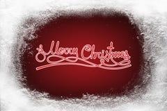 Wesoło bożych narodzeń tekst na czerwonym tła i hoarfrost śniegu oszroniejącym na xmas okno Zdjęcia Stock