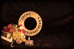 ` Wesoło bożych narodzeń ` w niemiec z postacią, choinek piłkami i świeczką, Obrazy Royalty Free