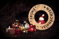 ` Wesoło bożych narodzeń ` w niemiec z postacią, choinek piłkami i świeczką, Zdjęcia Stock